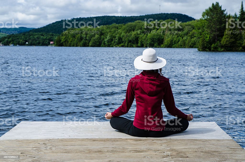 Woman relaxing at the end of dock stock photo