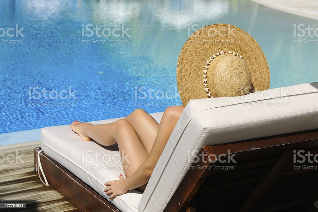 Woman relaxing at the poolside stock photo