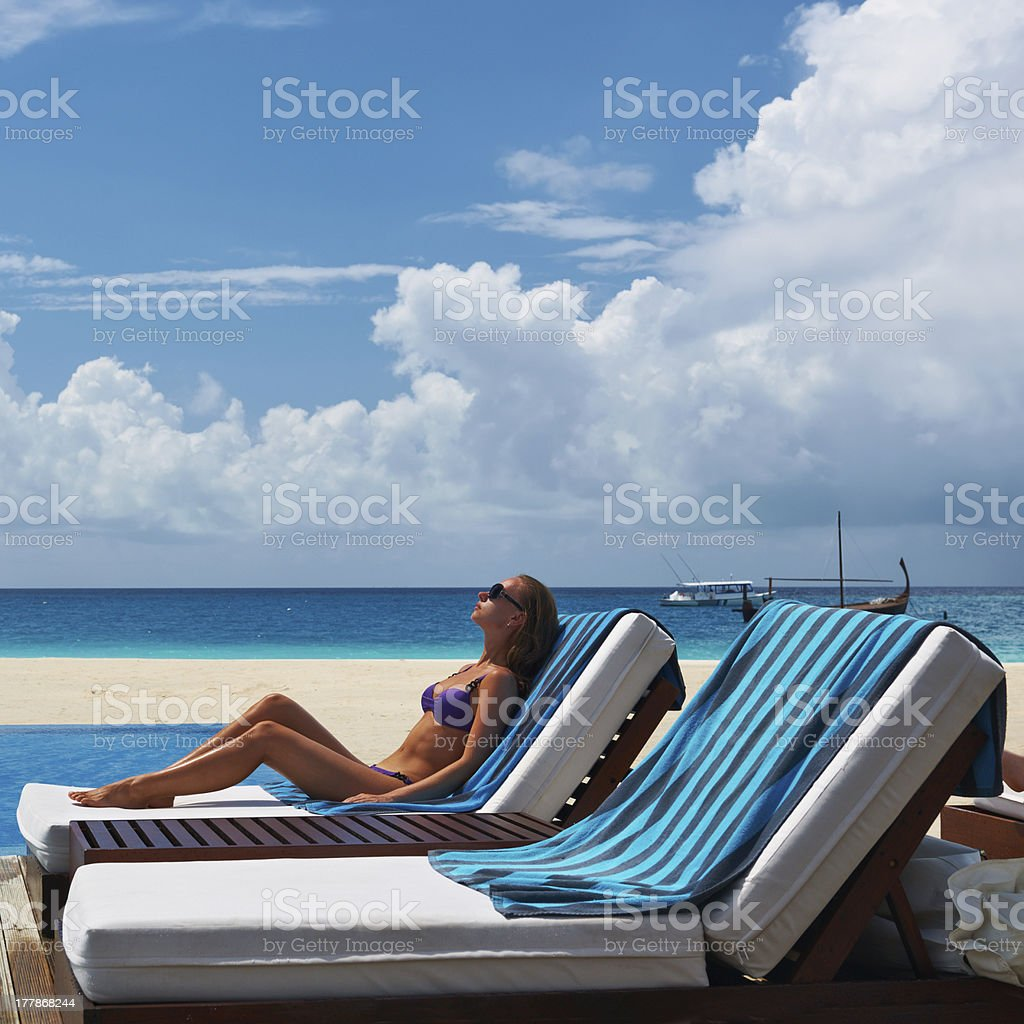 Woman relaxing at the poolside royalty-free stock photo