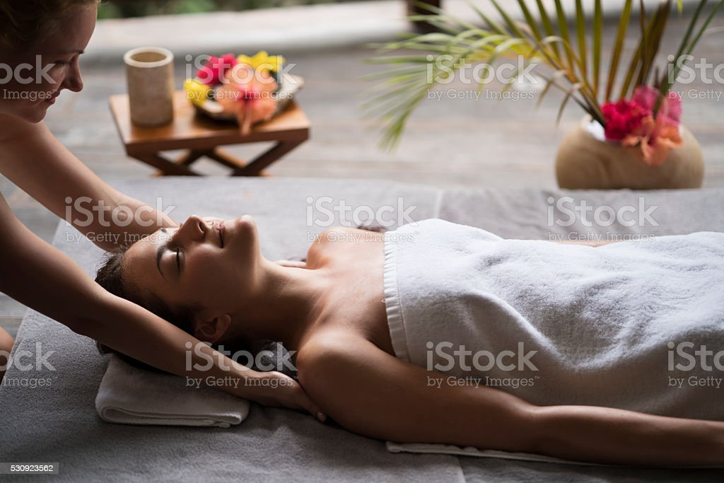 Woman relaxing at the spa while receiving a back massage. stock photo