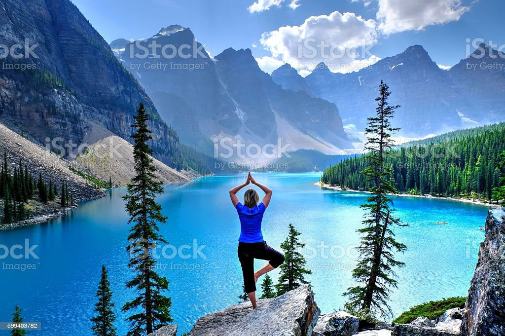 Woman relaxing by lake and mountains. stock photo