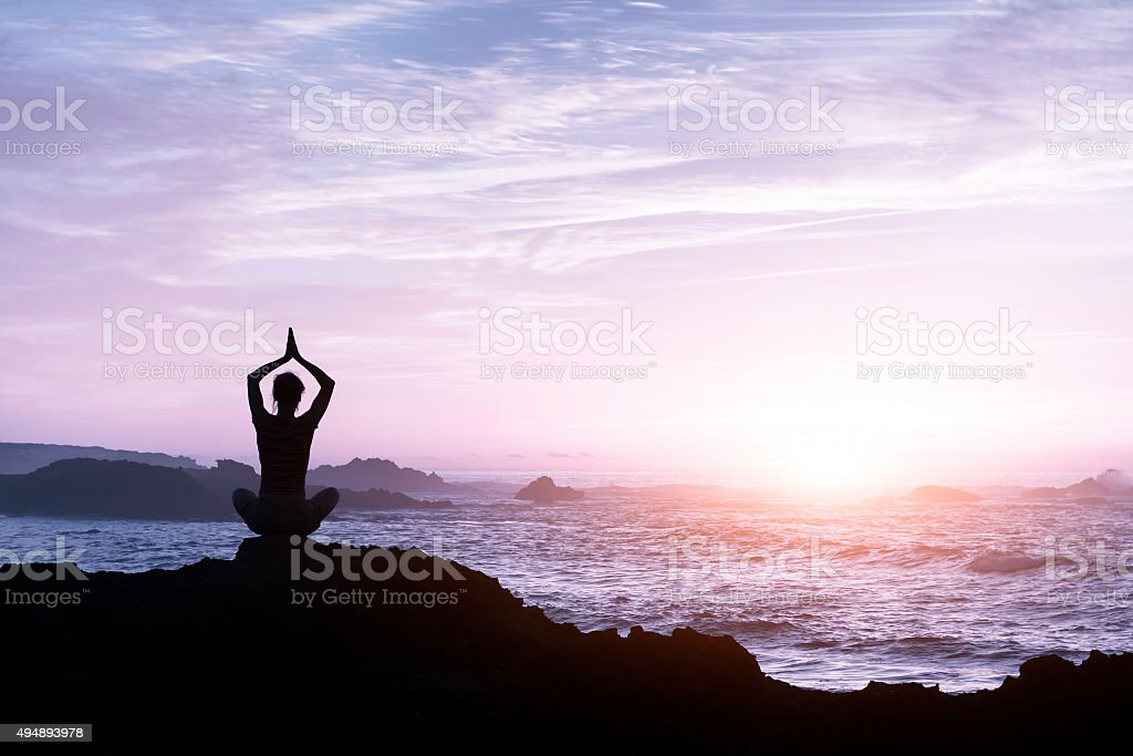 Woman relaxing by practicing yoga near the sea stock photo