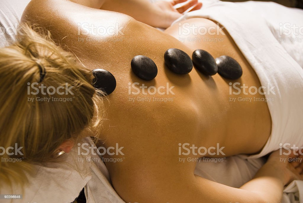 Woman relaxing during a hot stone massage royalty-free stock photo