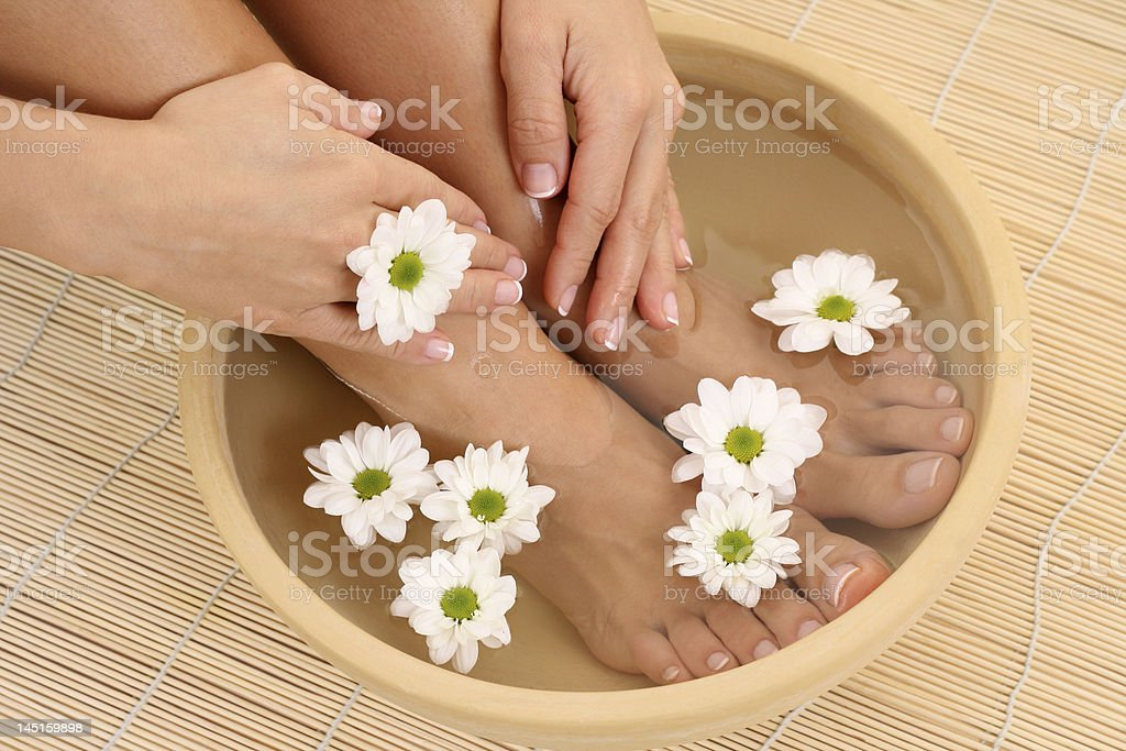 A woman relaxing her feet in warm water with flowers royalty-free stock photo