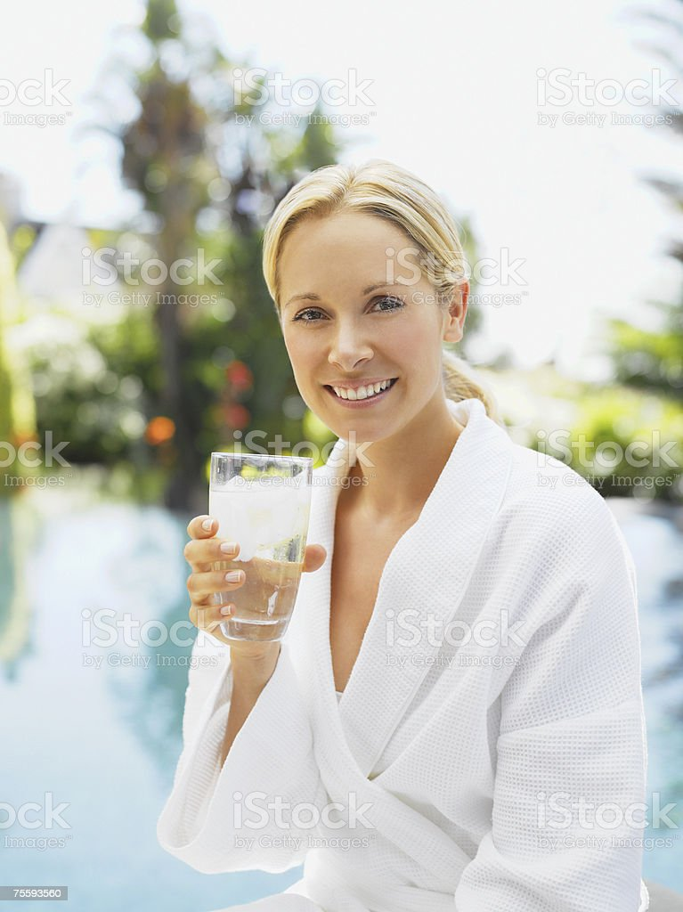 Woman relaxing in a bathrobe by a pool royalty-free stock photo
