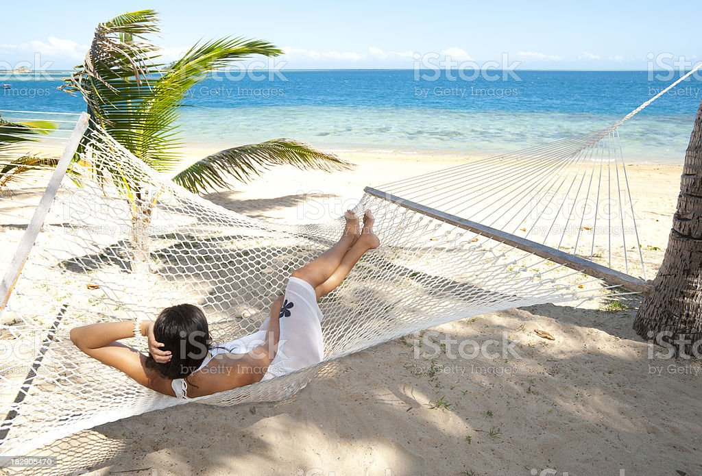 Woman relaxing in a hammock on the beach royalty-free stock photo