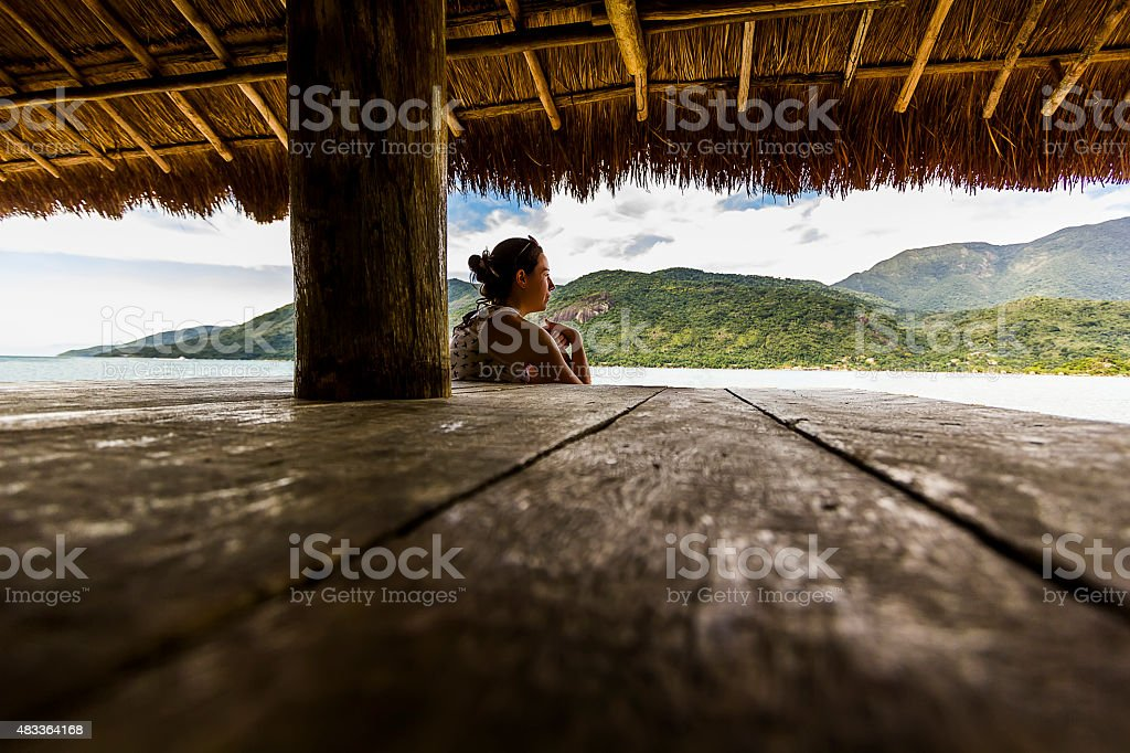 Woman Relaxing in a Hut Watching the Sea stock photo
