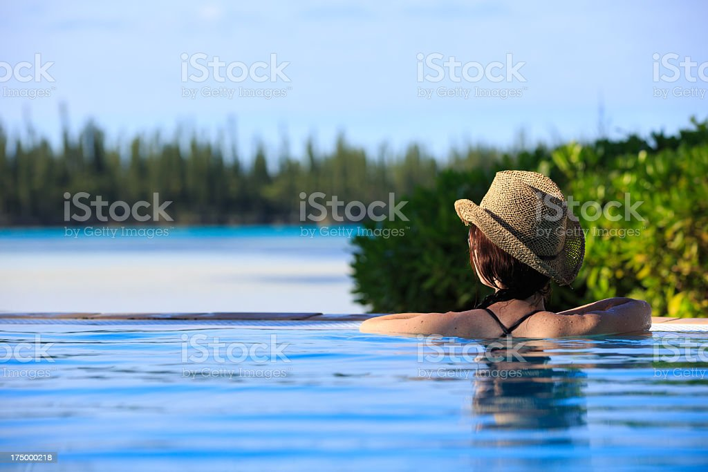 Woman Relaxing in a Tropical Infinity Swimming Pool royalty-free stock photo