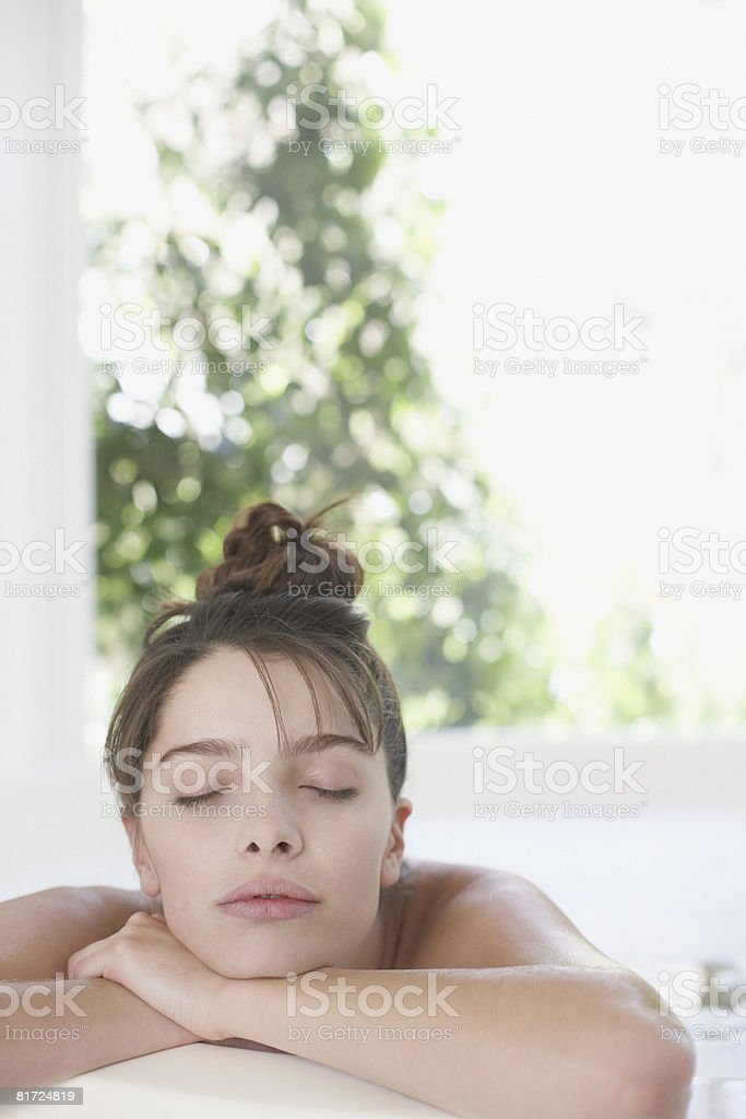 Woman relaxing in bath with eyes closed royalty-free stock photo