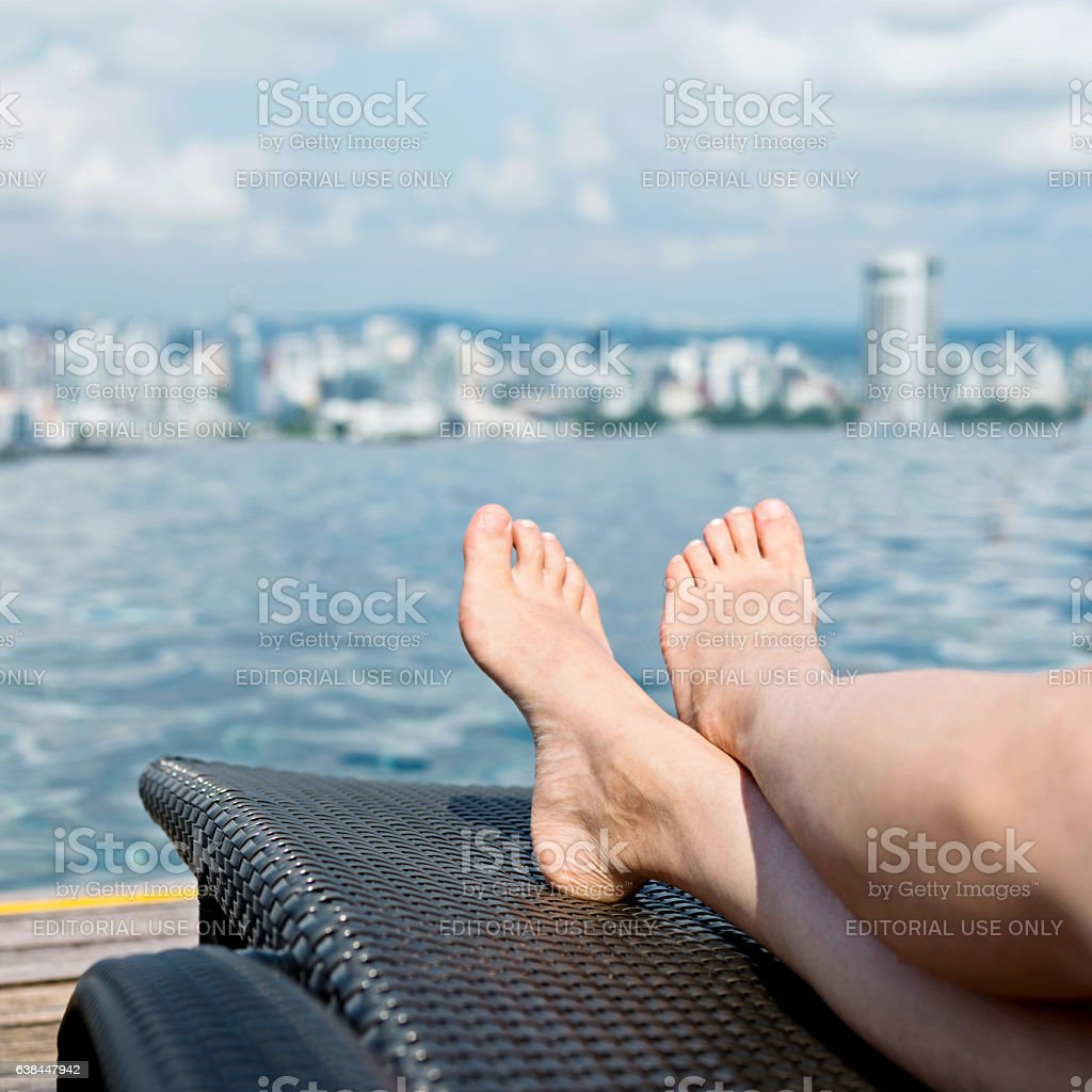 Woman relaxing in city infinity pool stock photo
