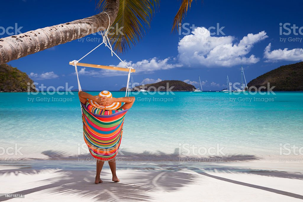 woman relaxing in colorful hammock at a tropical beach royalty-free stock photo