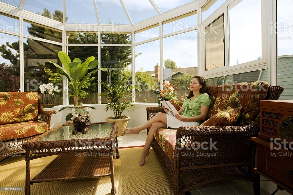 Woman Relaxing in Cozy Conservatory stock photo