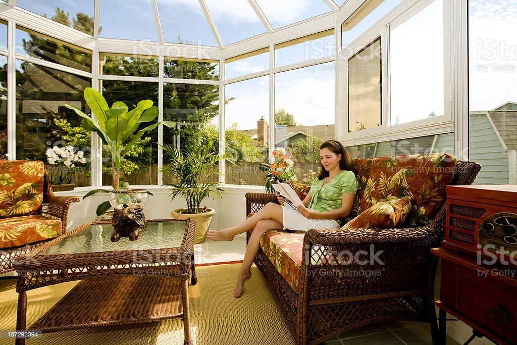 Woman Relaxing in Cozy Solarium stock photo