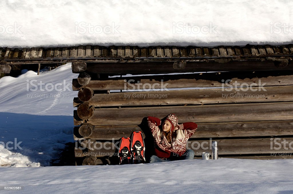 Woman relaxing in front of alpine hut stock photo