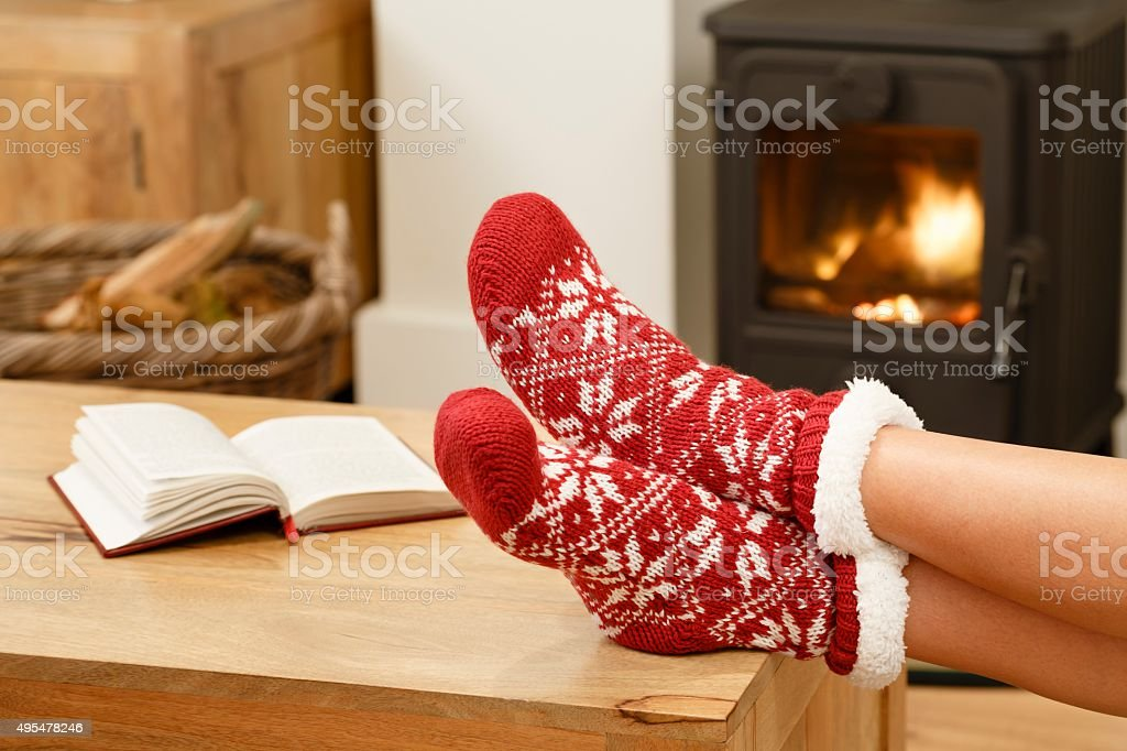 Woman relaxing in front of fire stock photo