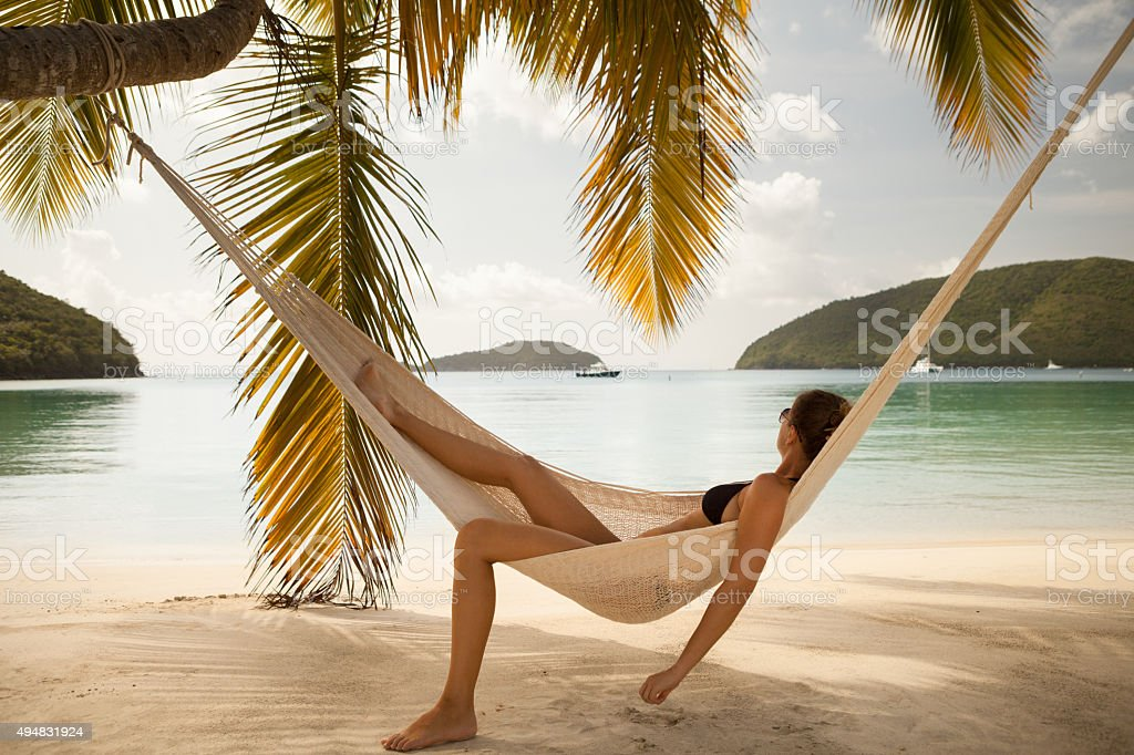 woman relaxing in hammock at Maho Bay Beach, St.John, USVI stock photo