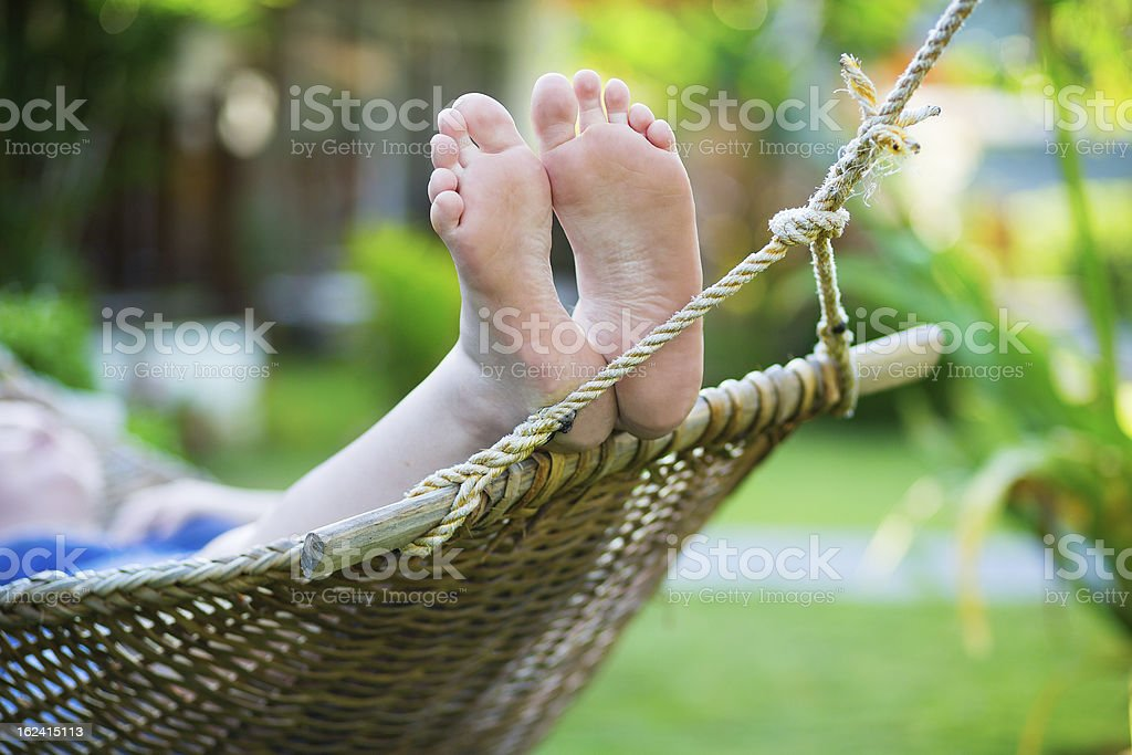 Woman relaxing in hammock on a tropical resort royalty-free stock photo