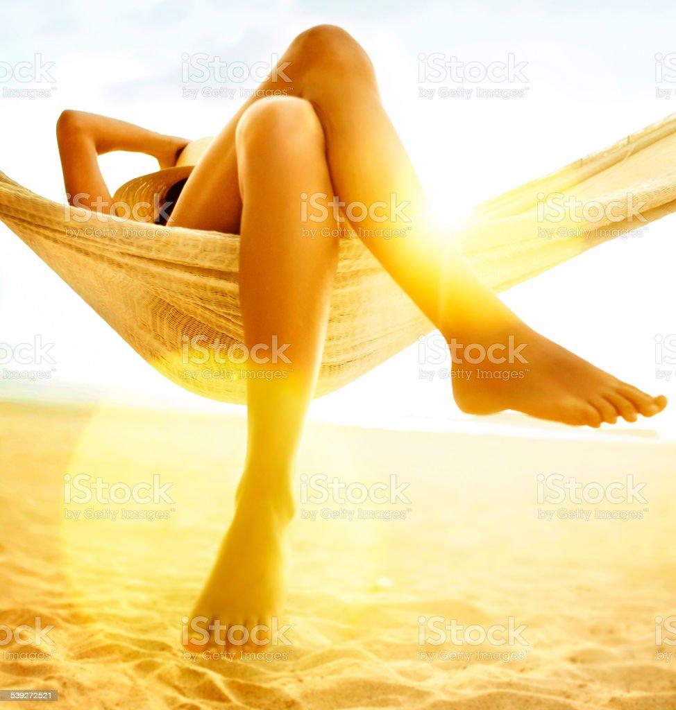 Woman relaxing in hammock on beach stock photo