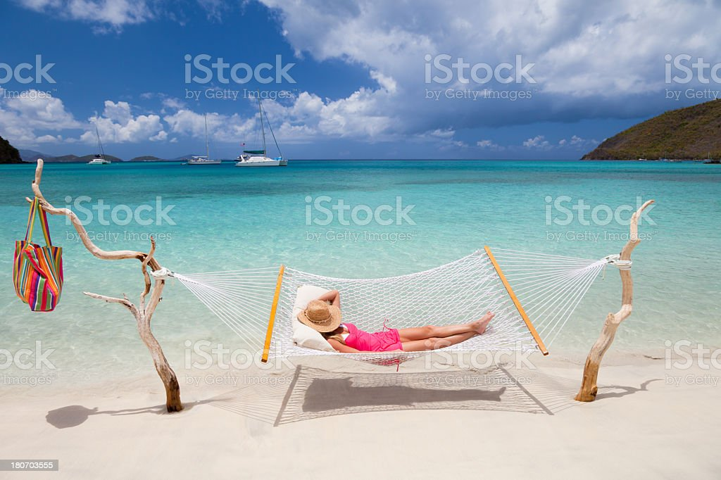 woman relaxing in hammock stretched between two pieces of driftwood royalty-free stock photo