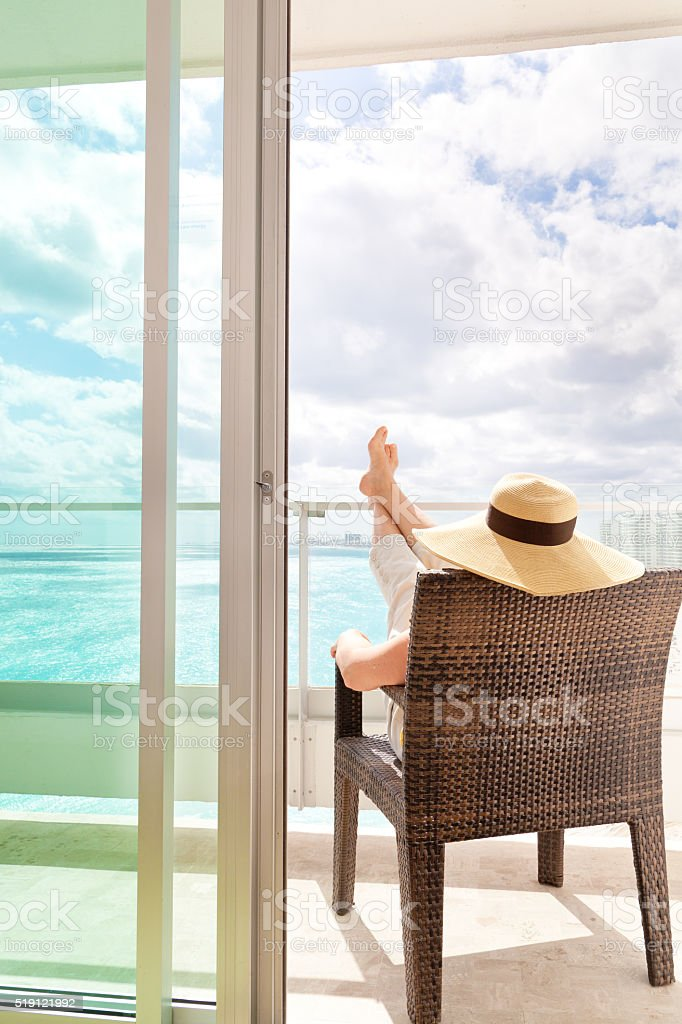 Woman Relaxing in Hotel Balcony of Beach Resort stock photo