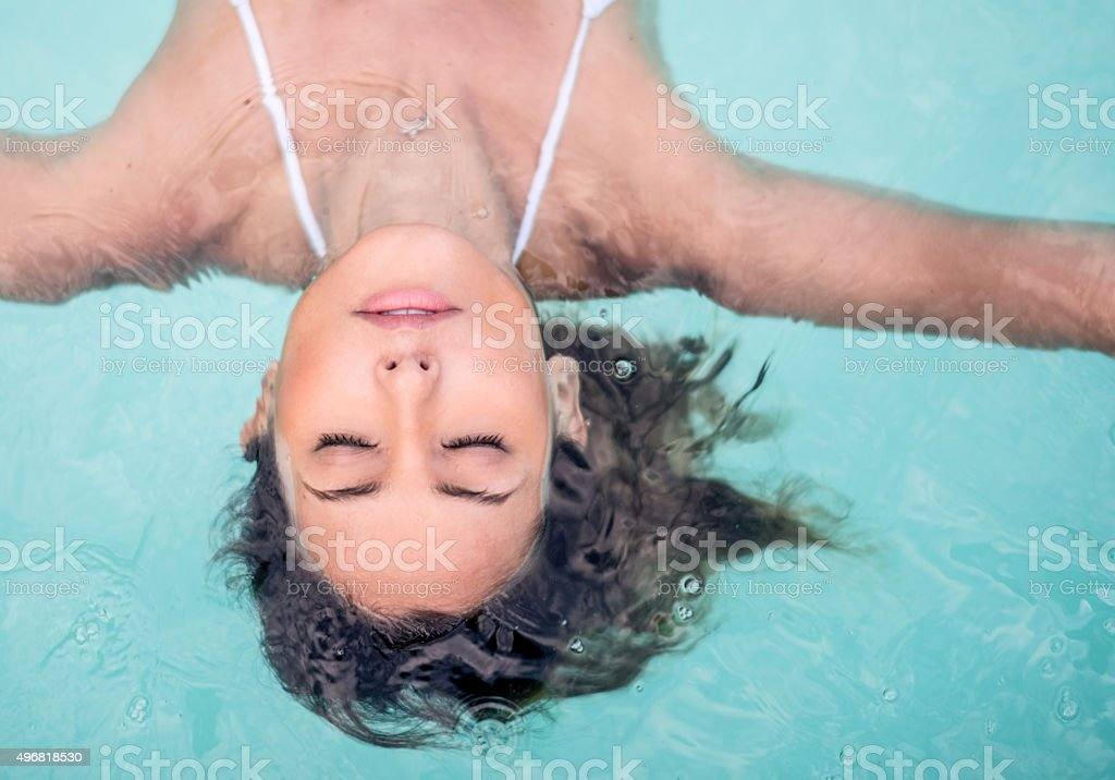 Woman relaxing in the swimming pool stock photo