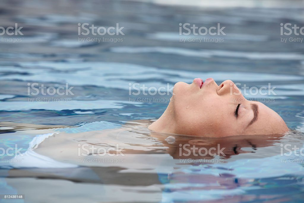Woman relaxing in tropical ocean stock photo
