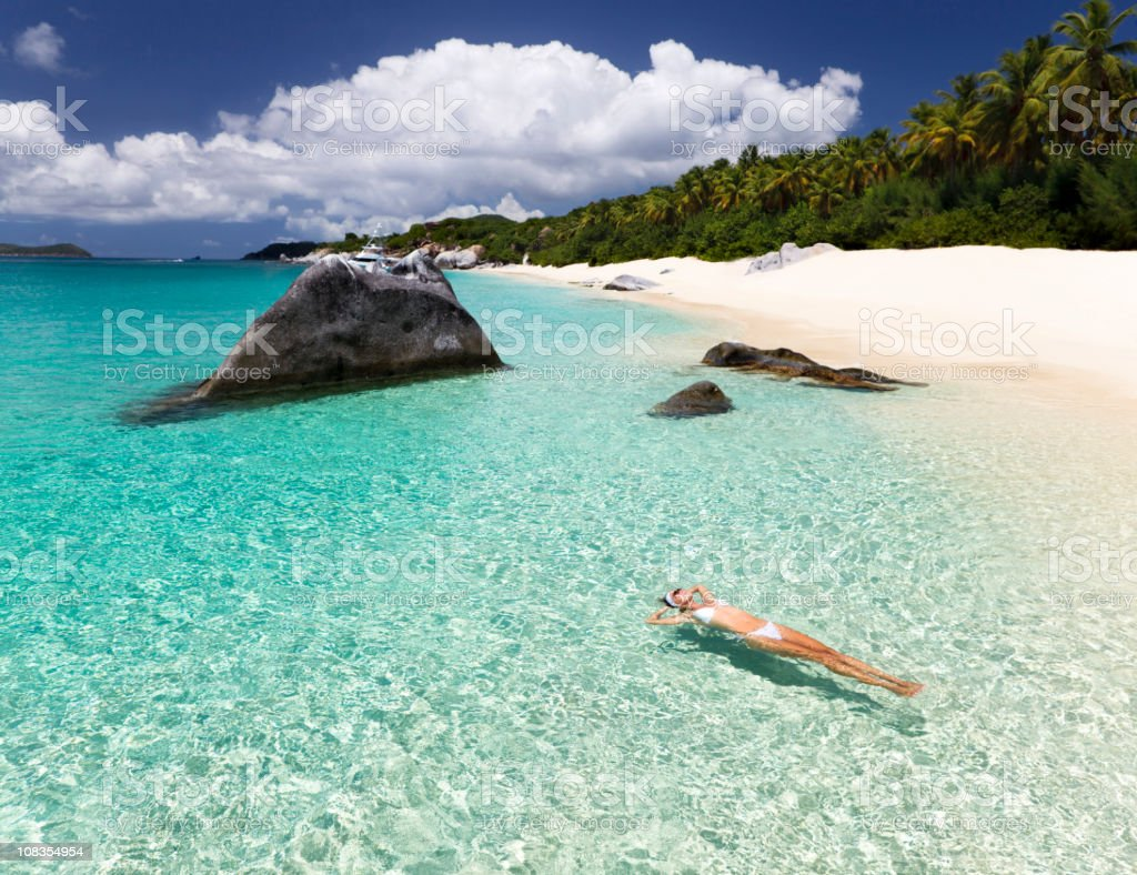 woman relaxing in water at a Caribbean beach stock photo