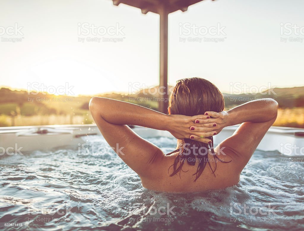 Woman relaxing in whirlpool jacuzzi stock photo