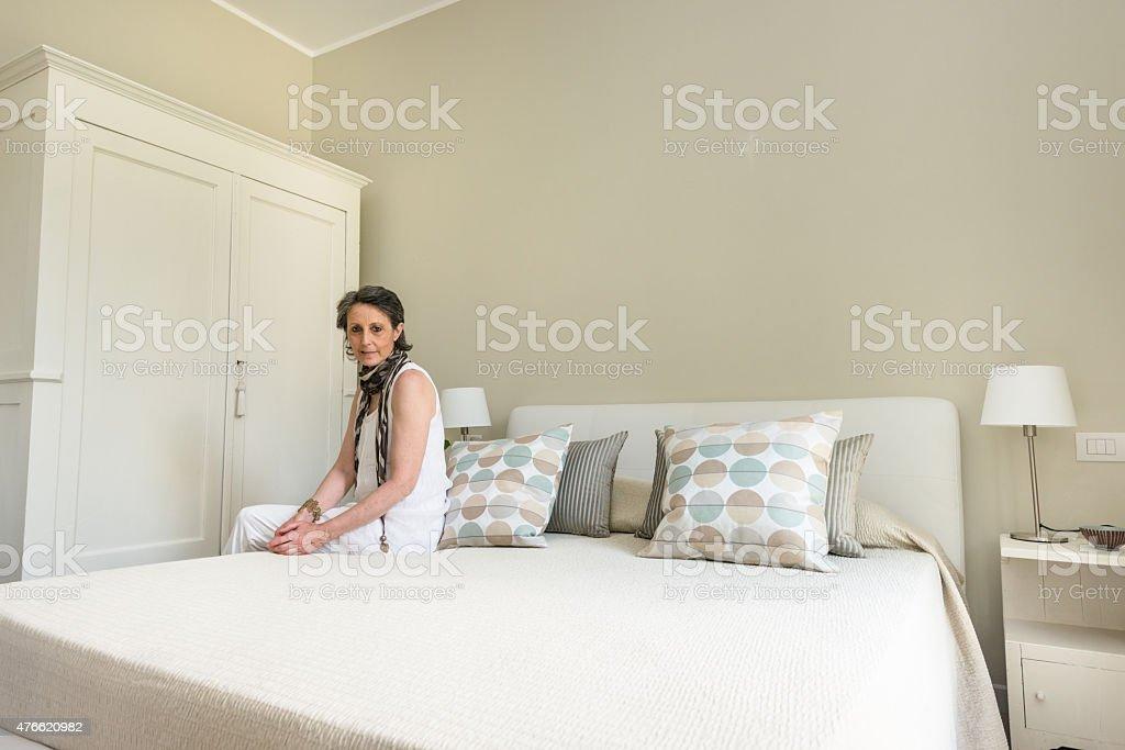 Woman relaxing inside her beautiful bedroom stock photo