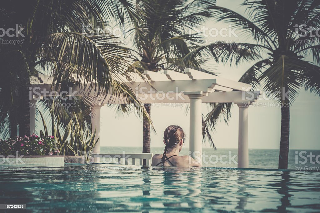 Woman Relaxing Inside Infinity Pool At Tropical Resort stock photo