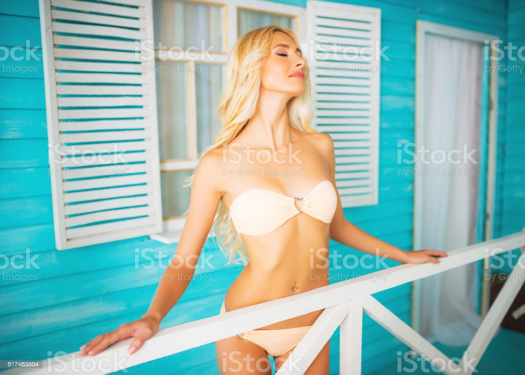 Woman relaxing near bungalows stock photo