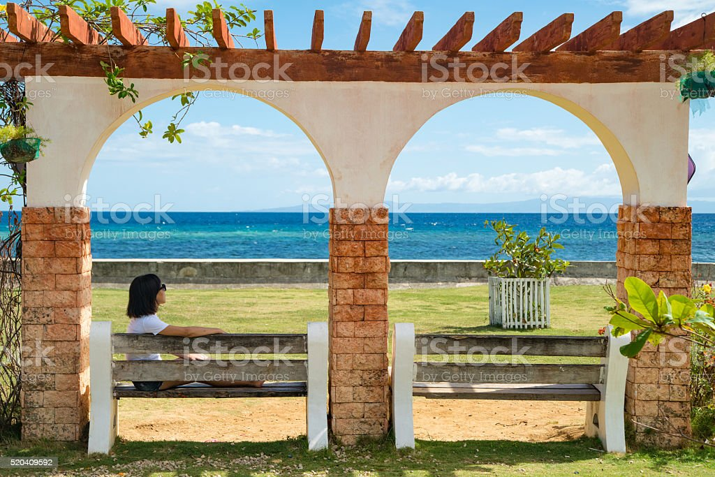 Woman relaxing on a bench by the ocean stock photo