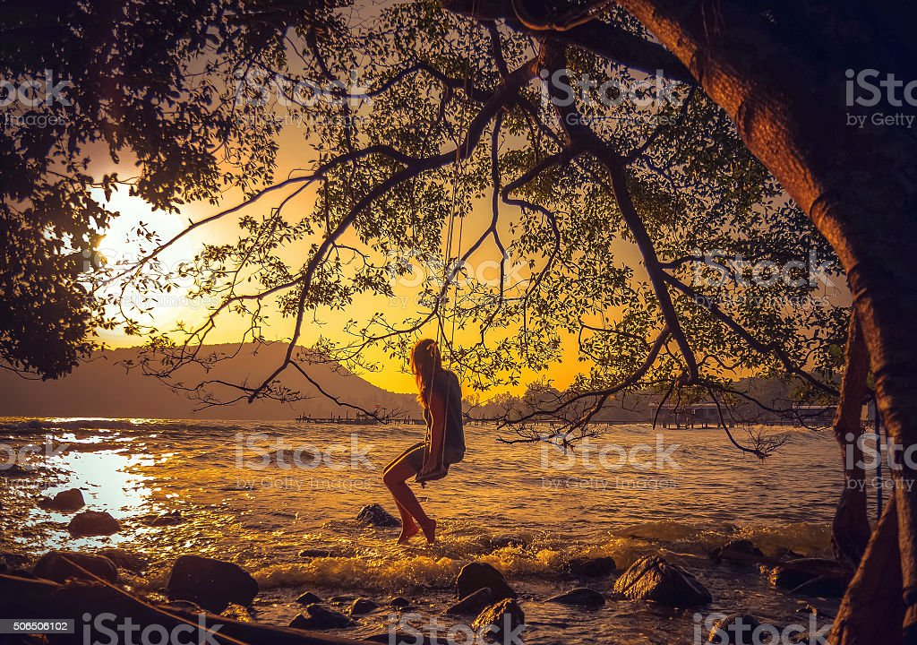 Woman relaxing on a swing on the beach stock photo