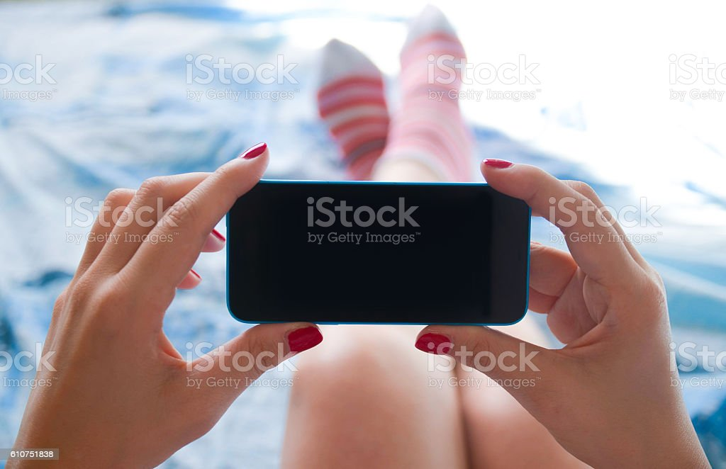 Woman relaxing on bed with smartphone royalty-free stock photo