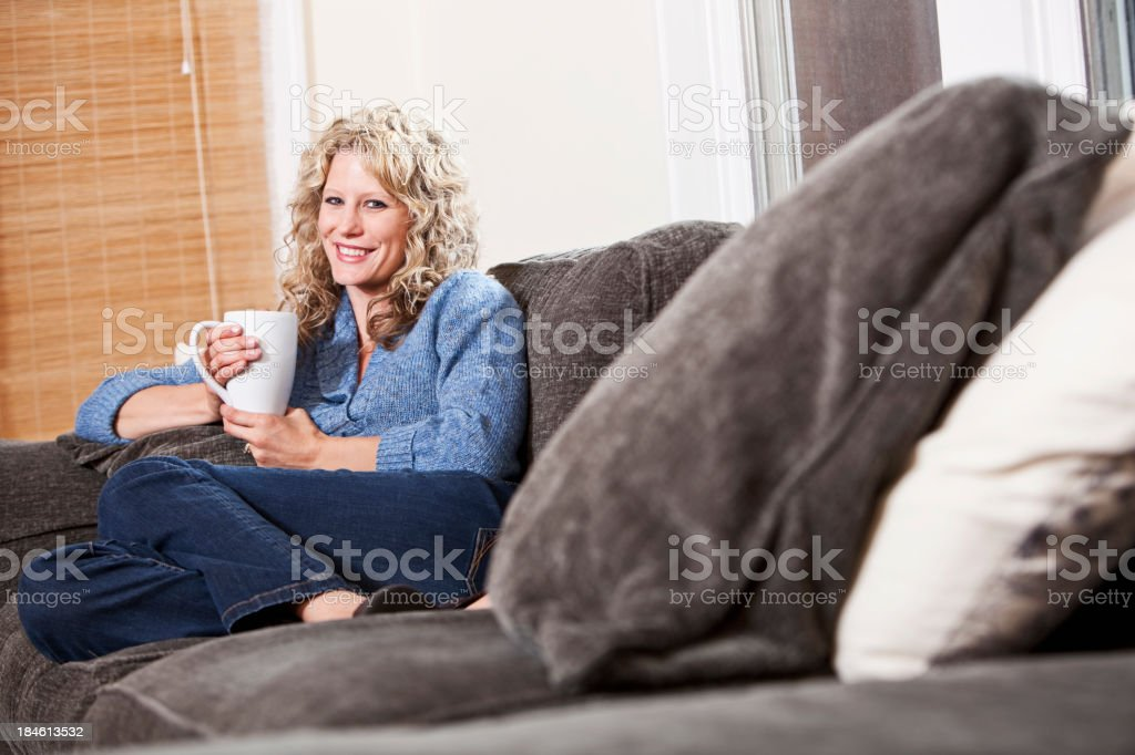 Woman relaxing on couch with coffee mug stock photo