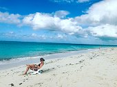 Woman relaxing on Grace Bay Beach, Turks and Caicos