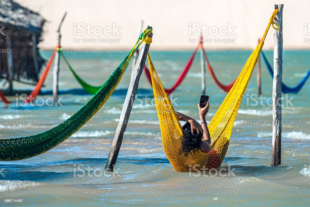 Woman relaxing on hammock, Jericoacoara, Brazil stock photo