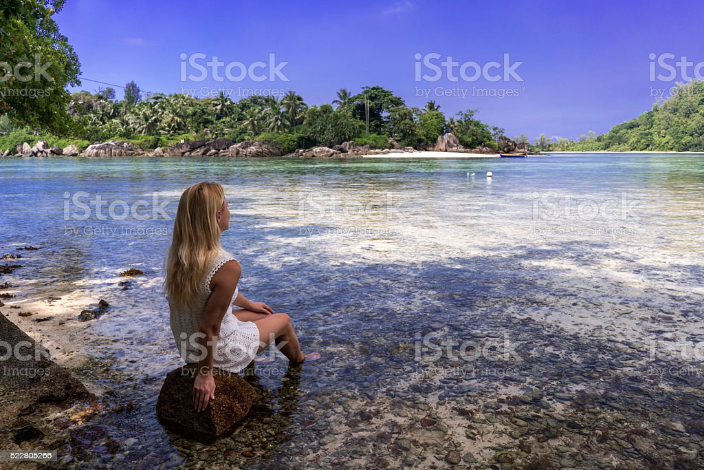 Woman relaxing on rock and looking at La Digua island. stock photo