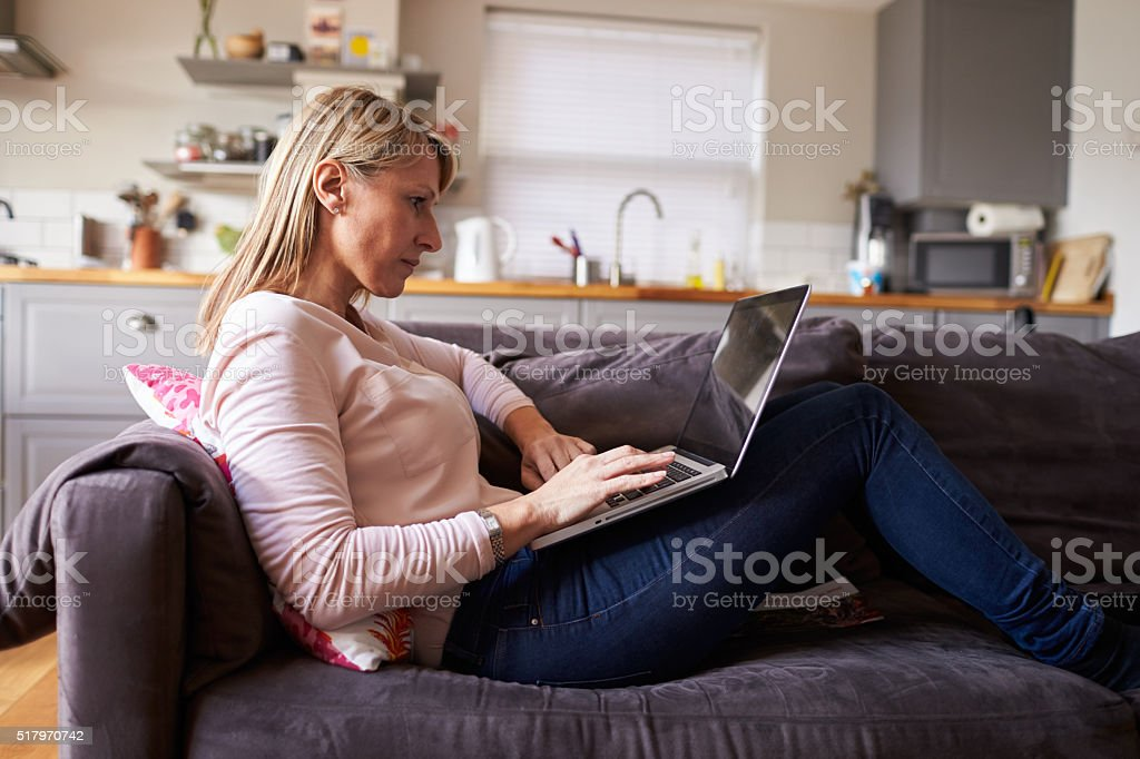 Woman Relaxing On Sofa Using Laptop In Modern Apartment stock photo
