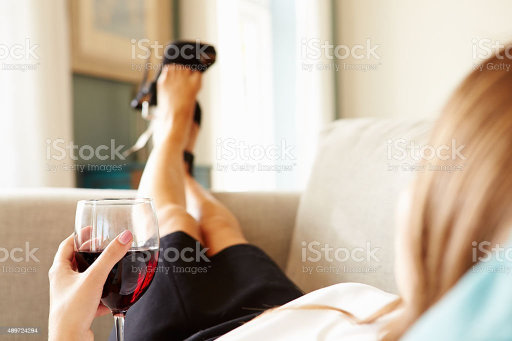 Woman Relaxing On Sofa With Glass Of Wine After Work stock photo