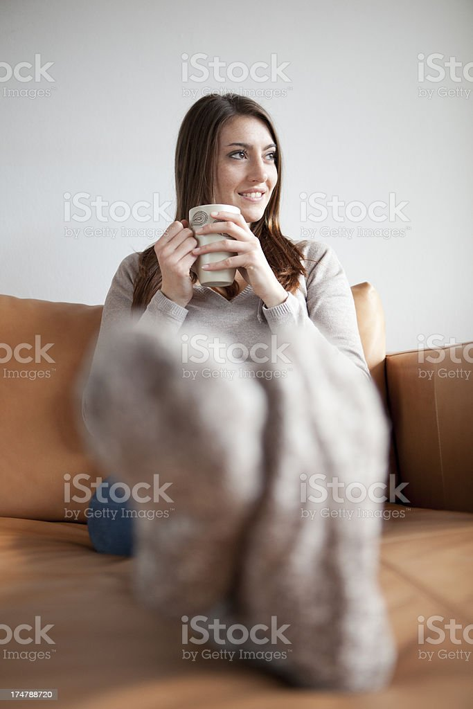 Woman relaxing on sofa with wool socks and tea royalty-free stock photo
