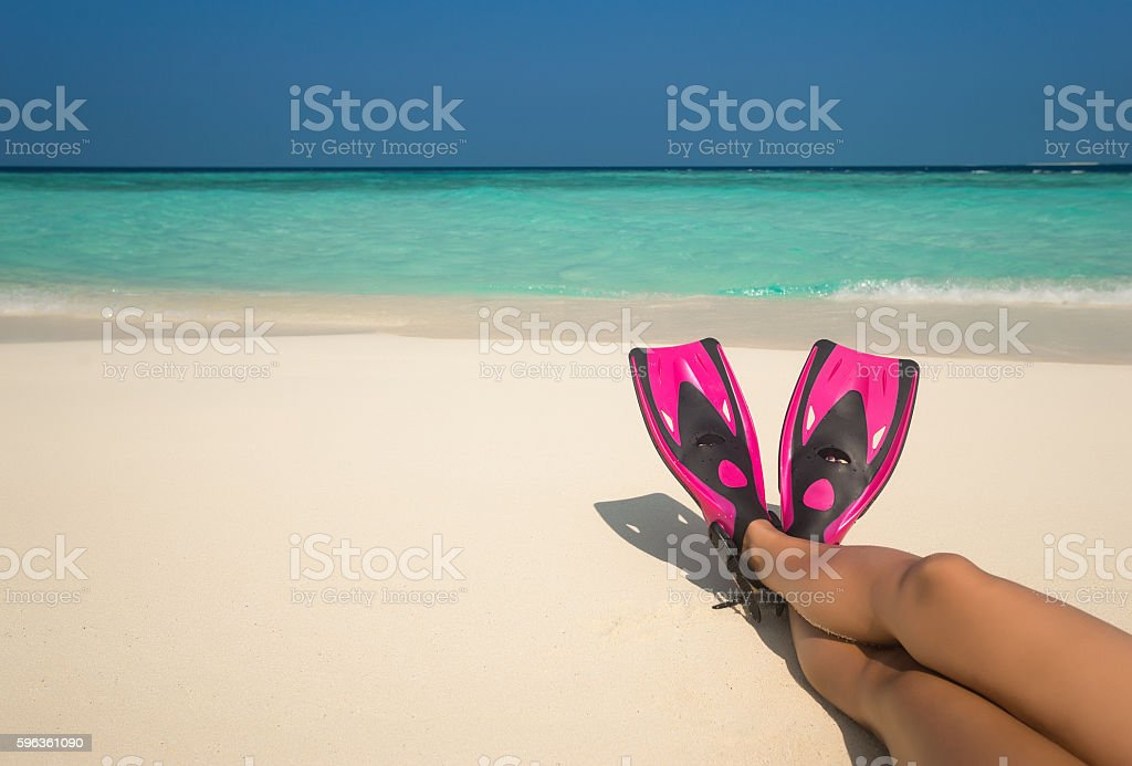 Woman relaxing on summer beach vacation holidays lying in sand. stock photo