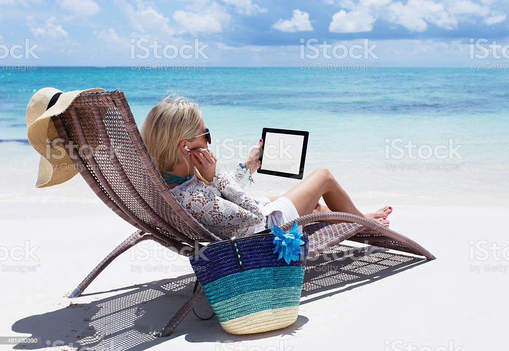 Woman relaxing on the beach and listening to music stock photo