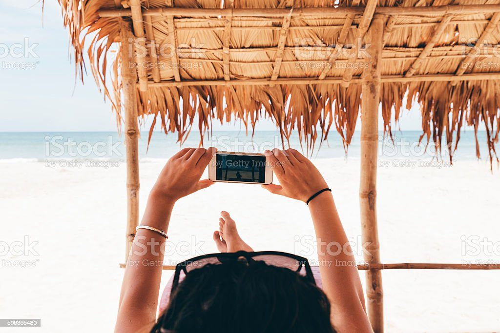 Woman Relaxing On The Beach Take Picture. stock photo