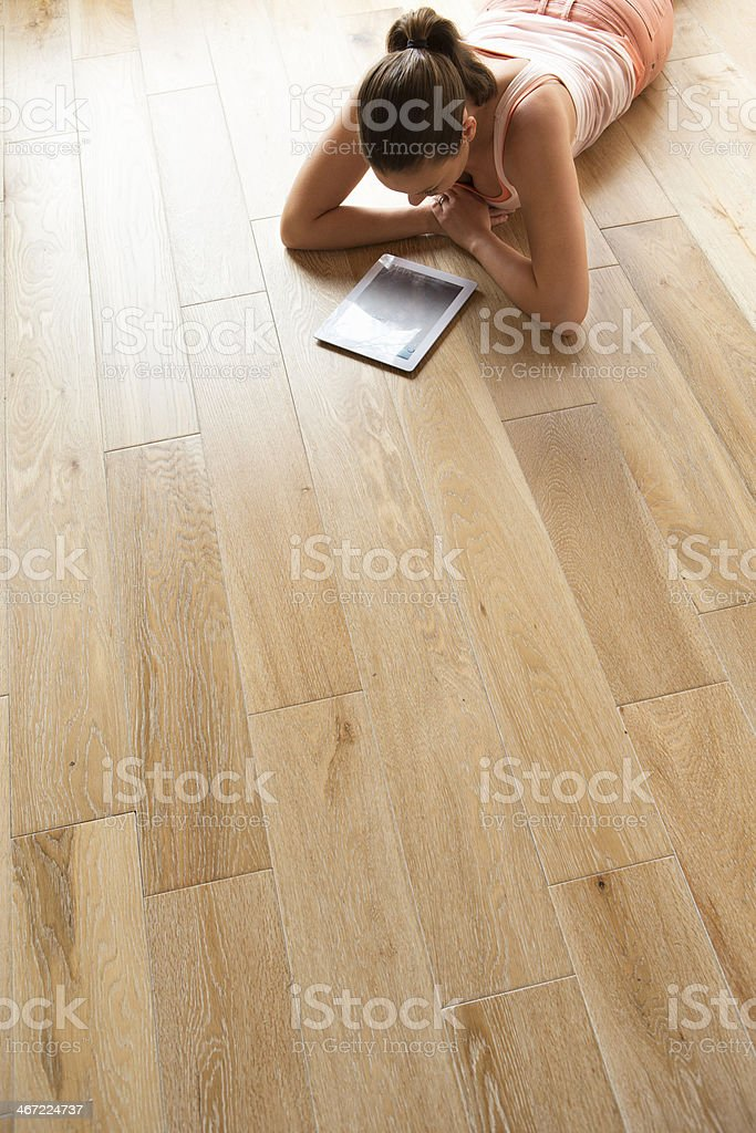 Woman relaxing on Wood Flooring with digital tablet royalty-free stock photo