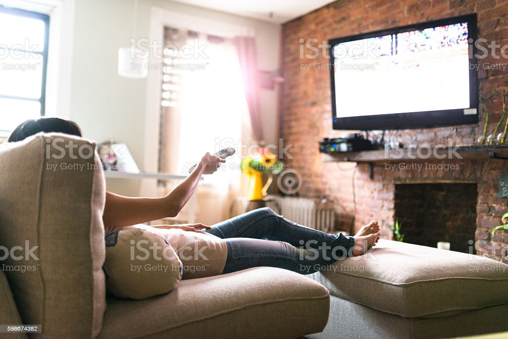 woman relaxing online on sofa reading some papers stock photo