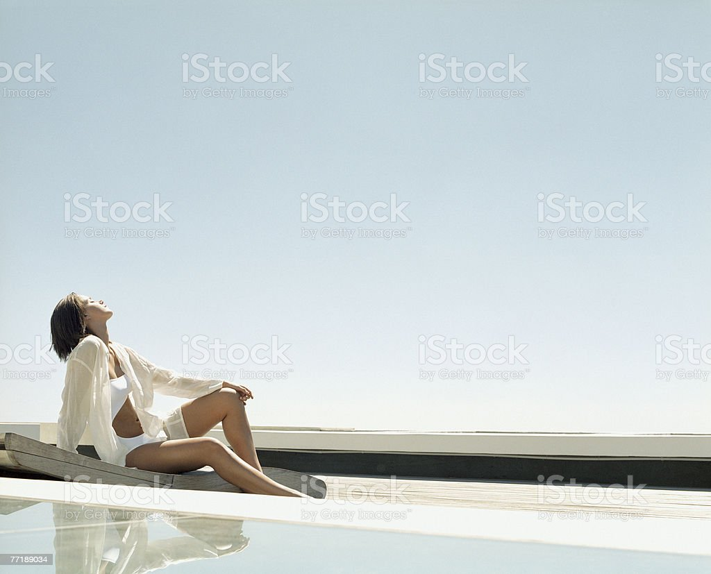 A woman relaxing poolside royalty-free stock photo