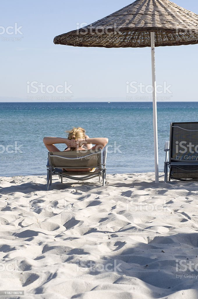 Woman relaxing under parasol on sunlounger at beach, rear view royalty-free stock photo