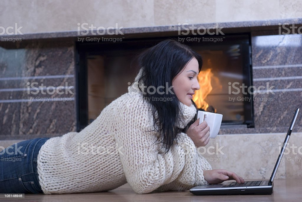 Woman relaxing while drink coffee and working on a laptop royalty-free stock photo