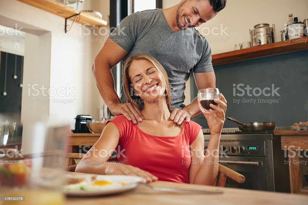 Woman relaxing while man massaging her shoulders stock photo